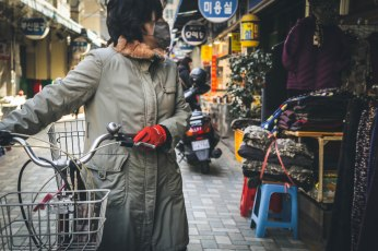 A woman with a bicycle in a street market in Busan.